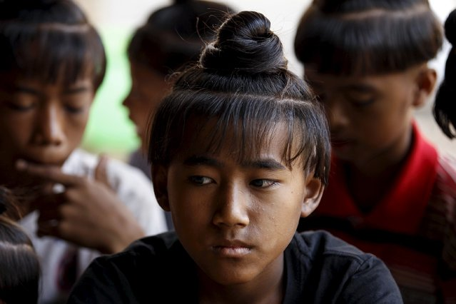 Zaw Myo Aung (C), 13, sits with others boys who all sport the ancient hairstyle known as Sanyitwine in a monastery at Sat Sat Yo village in Nyaung Oo township, near Myanmar's ancient city Bagan April 17, 2015. (Photo by Soe Zeya Tun/Reuters)