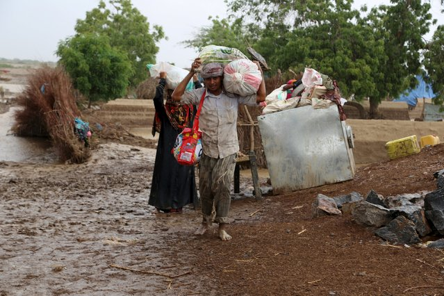 People carry their belongings as they evacuate from a flooded village following heavy rain in Yemen's Red Sea province of Houdieda April 15, 2016. (Photo by Abduljabbar Zeyad/Reuters)