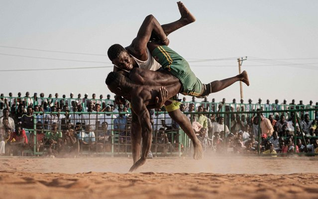 Sudanese wrestlers fight during a traditional Nuba wrestling match at the Haj Youssef stadium in the district of Khartoum on June 21, 2019. Originating in the Nuba mountains, the sport has become wildly popular country-wide in recent years. The Sudanese Nuba wrestling federation organizes matches every Friday that attract hundreds of people. (Photo by Yasuyoshi Chiba/AFP Photo)