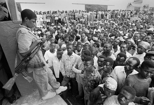 Rebels hold a victory rally in Goma, Zaire. A very young rebel soldier stands watch over the crowd; 1996. (Photo by Carol Guzy/The Washington Post)