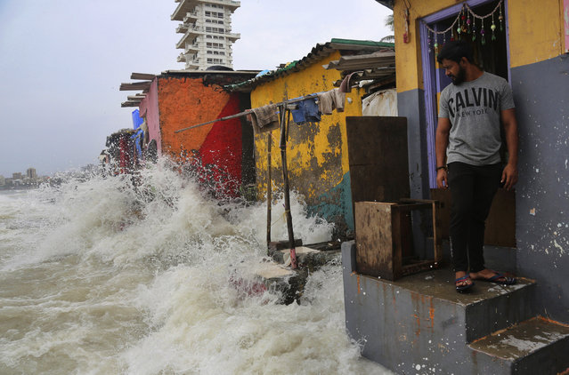 An Indian man stands near his house as waves caused by high tide hits the huts on the shore of the Arabian Sea in Mumbai, India, Wednesday, July 3, 2019. Heavy monsoon rains in Maharashtra have led to more than 30 deaths since Monday night, from collapsed walls, drownings and other causes. Dozens of others have been injured. (Photo by Rafiq Maqbool/AP Photo)
