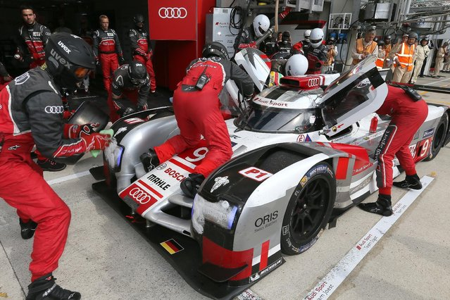 Mechanics refuel the Audi R18 E-TRON Quattro No9 driven by Filipe Albuquerque of Portugal, Marco Bonanomi of Italy and Rene Rast of Germany during a stop in the pits during the 83rd 24-hour Le Mans endurance race, in Le Mans, western France, Saturday, June 13, 2015. (AP Photo/David Vincent)