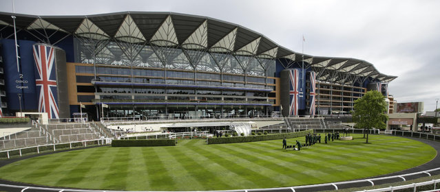 Gatekeeprs assemble for a group photograph in the parade ring on the second day of  Royal Ascot horse racing meet at Ascot, England, Wednesday, June 17, 2015. Royal Ascot is the annual five-day horse race meeting that Britain's Queen Elizabeth II attends every day of the event. (AP Photo/Alastair Grant)