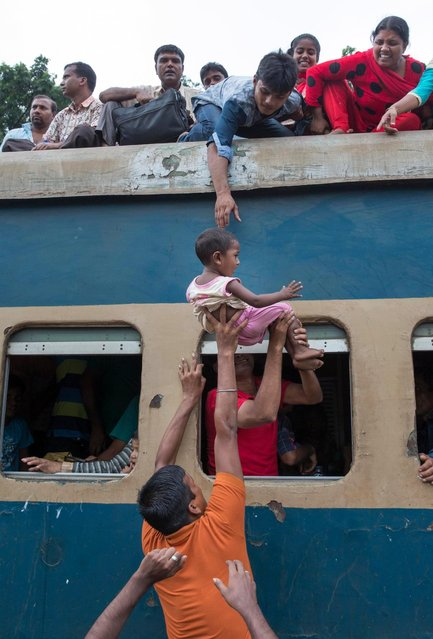 A young lad gets a helping hand as the desperate passengers attempt to bag a space on the heavily-laden locomotive. (Photo by Yousuf Tushar/Solent News & Photo Agency)