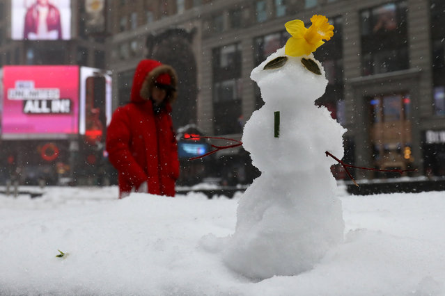 A person walks with an umbrella past a snowman during a snow storm in Times Square in Manhattan, New York, U.S., March 14, 2017. (Photo by Carlo Allegri/Reuters)