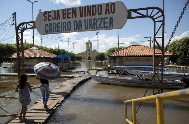 Residents walk on a makeshift walkway above a flooded street from the rising Rio Solimoes, one of the two main branches of the Amazon River, in Careiro da Varzea of Amazonas State, Brazil, June 30, 2015. (Photo by Bruno Kelly/Reuters)
