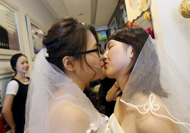 Li Tingting (R) and Teresa kiss while wearing bridal gowns at a bridal photography studio in Beijing, China July 2, 2015. (Photo by Kim Kyung-Hoon/Reuters)