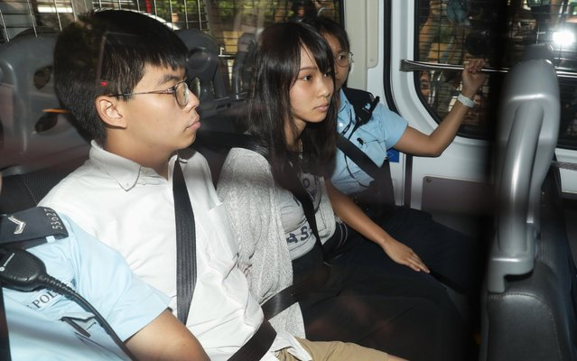 Pro-democracy activists Joshua Wong, left, and Agnes Chow, are escorted in a police van at a district court in Hong Kong, Friday, August 30, 2019. Hong Kong police arrested well-known activist Wong and Chow, another core member of a pro-democracy group, Friday, and authorities denied permission for a major march in what appears to a harder line on this summer's protests. (Photo by Kyle Lam/Bloomberg)