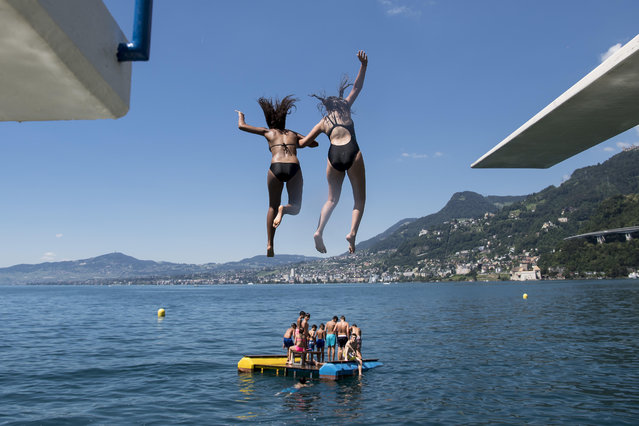 In this July 9, 2016 file photo, girls jump from a diving platform into the Geneva Lake and enjoy sunny and warm weather, in Villeneuve, Switzerland. After nearly 90 years, women can legally swim topless in Geneva's lake and Rhone River without running the risk of a fine. Geneva's regional council has voted to modify a 1929 ordinance that banned women from swimming topless in the city's main natural waterways, though the change doesn't apply to public swimming pools or swimming totally naked. Nicolas Bolle, an official with Geneva's security department, on Thursday, April 6, 2017 confirmed the council's action a day earlier. (Photo by Jean-Christophe Bott/Keystone via AP Photo)