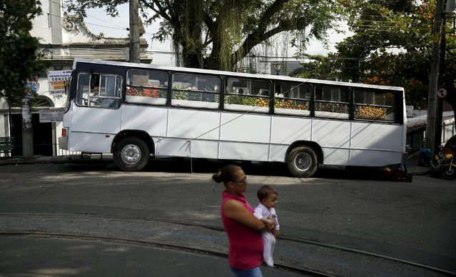 A woman holds her baby as she stands in front of a bus market called Sacolao in Santa Teresa neighborhood in Rio de Janeiro, Brazil, July 7, 2015. (Photo by Pilar Olivares/Reuters)