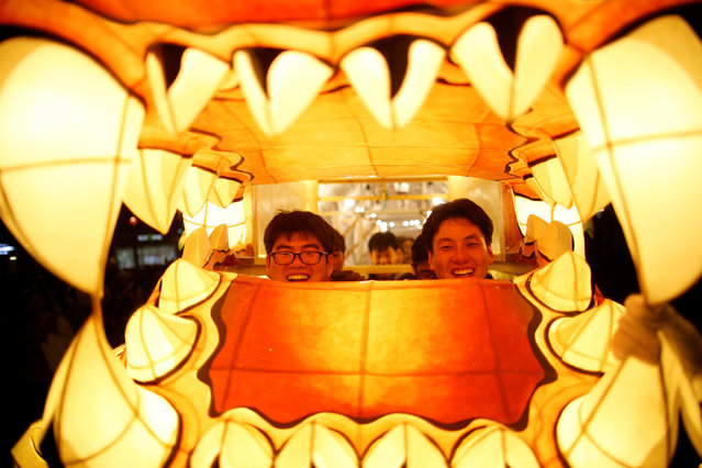 Buddhists inside a dragon-shaped lantern smile as they march during a lotus lantern parade in celebration of the upcoming birthday of Buddha in Seoul, South Korea, May 7, 2016. (Photo by Kim Hong-Ji/Reuters)