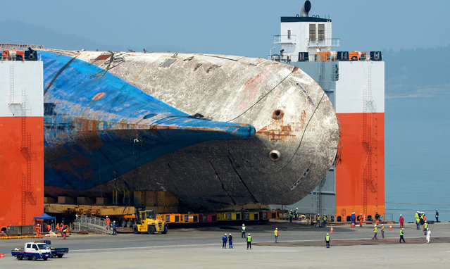 The salvaged Sewol ferry is moved onto land by module transporters to be put on a dry dock at a port in Mokpo, 410 km southwest of Seoul, South Korea, 09 April 2017. Sewol sank on 16 April 2014, killing more than 300 people, most of them high school students who were on a school excursion. The search for nine people still missing will commence after the ferry is anchored on land. (Photo by EPA/Yonhap)