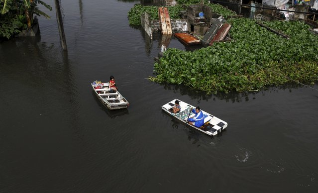 Residents ride on makeshift boats as they make their in Artex Compound, the lowest point in the city which is prone to flooding during monsoon seasons, in Malabon, Metro Manila in the Philippines July 11, 2015. (Photo by Lorgina Minguito/Reuters)