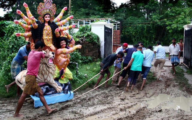 Indian devotees pull a clay idol of the Hindu Goddess Durga across a muddy area following rains in Allahabad on September 28, 2019. (Photo by Sanjay Kanojia/AFP Photo)
