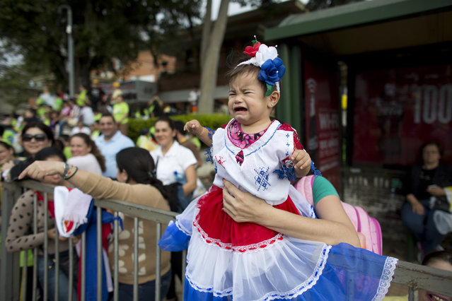 Daniela Romero, 7-months-old, cries in the arms of her mother as they wait for Pope Francis to pass on his popemobile in Asuncion, Paraguay, Saturday, July 11, 2015. Pope Francis lauded the strength and religious fervor of Paraguayan women on Saturday while visiting the country's most important pilgrimage site, where thousands of his fellow Argentines joined with hundreds of thousands of local faithful to welcome Latin America's first pope. (Photo by Victor R. Caivano/AP Photo)
