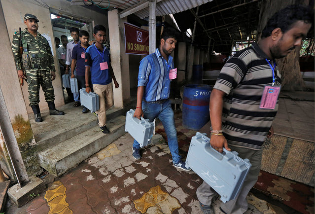 Election officials carry electronic voting machines (EVM) as they arrive to count votes in the West Bengal Assembly elections, at a counting center in Kolkata, India May 19, 2016. (Photo by Rupak De Chowdhuri/Reuters)