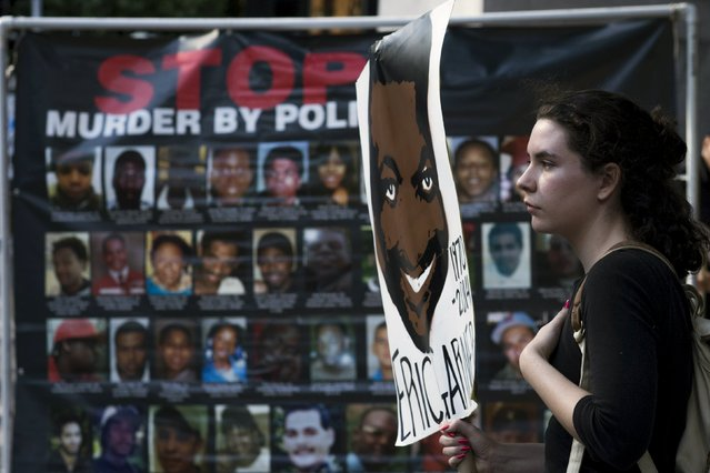 A protester holds a placard with an image of Eric Garner during his anniversary after being killed one year ago by police in New York July 17, 2015. (Photo by Eduardo Munoz/Reuters)