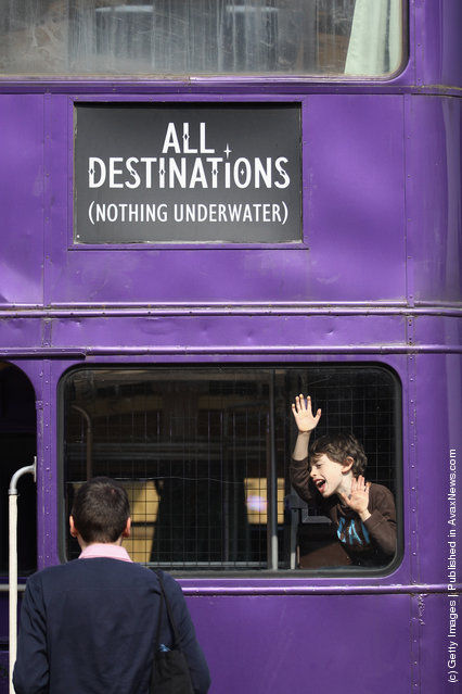 A boy plays on the 'Knight Bus', a purple triple decker bus used in the 'Harry Potter and the Prisoner of Azkaban', at the Harry Potter Studio Tour at Warner Brothers Leavesden Studios