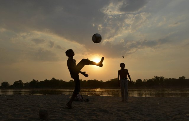 A group of Pakistani children play football by the Ravi River in Lahore on May 25, 2014. (Photo by Arif Ali/AFP Photo)