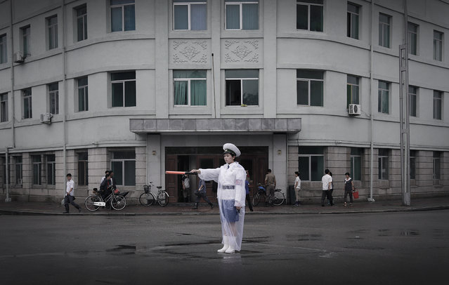 A traffic police woman dressed in a raincoat directs traffic, Saturday, July 25, 2015, in Pyongyang, North Korea. The rainy season in North Korea usually lasts through the month of July. (Photo by Wong Maye-E/AP Photo)
