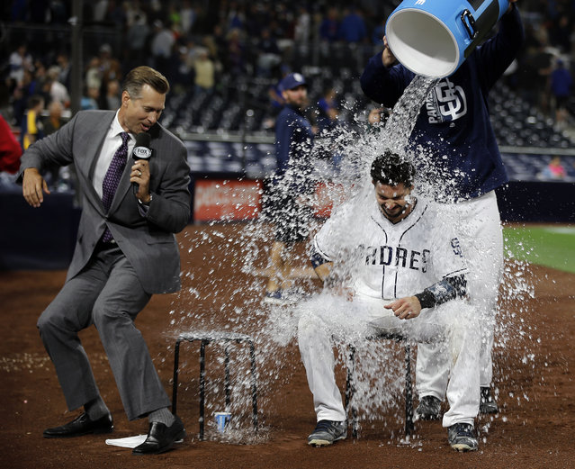 San Diego Padres' Austin Hedges, right, gets drenched by a bucket of liquid by Ryan Buchter as sideline reporter Bob Scanlan gets out of the way in a baseball game in San Diego, Tuesday, May 30, 2017. The Padres won, 6-2. (Photo by Alex Gallardo/AP Photo)