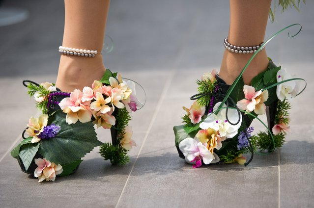 "A man walks with flower decorated High Heels in Berlin during the ""Drag Walk Casting"" ahead of the Christopher Street Parade on June 18, 2014. The Christopher Street Day takes place on June 21, 2014. (Photo by Daniel Naupold/AFP Photo/DPA)"