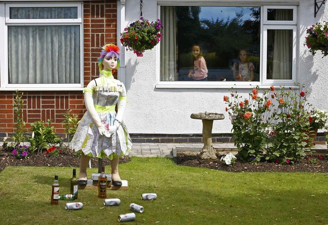 "Girls look from a window at scarecrow titled ""One for the road"" during the Scarecrow Festival in Heather, Britain July 29, 2015. (Photo by Darren Staples/Reuters)"