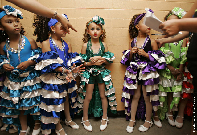 Anissa Delsi, 7, center, receives directions backstage along with fellow dancers prior to taking the stage at the Tucson Music Hall for a performance by the Viva Performance Art Center