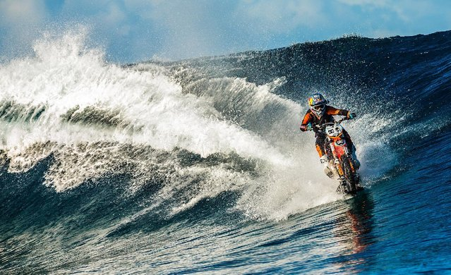 In this April, 2015, photo provided by DC Shoes, daredevil Robbie Maddison in his latest stunt rides his motorcycle across waves in Tahiti, French Polynesia, using ski-like devices on his wheels. (Photo by Garth Milan/DC Shoes via AP Photo)