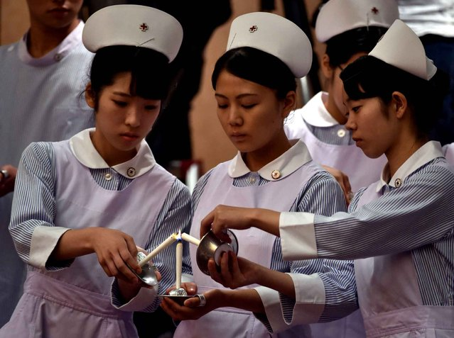Students of nursing schools hold candles during a candlelight ceremony before starting the awarding ceremony for the Florence Nightingale medal in Tokyo on August 5, 2015. Japanese Empress Michiko, honorary president of the Japanese Red Cross Society gave the medals to two distinguished Japanese nurses at the ceremony. (Photo by Yoshikazu Tsuno/AFP Photo)