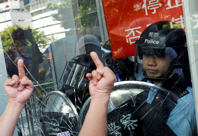 Protester gestures as he tries to break into the Legislative Council building where riot police are seen, during the anniversary of Hong Kong's handover to China in Hong Kong, China on July 1, 2019. (Photo by Thomas Peter/Reuters)