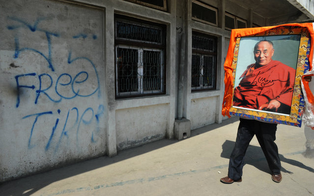 An exiled Tibetan carries a portrait of the Dalai Lama after celebrating the 23rd birthday of the Panchen Lama at the Tibetan Welfare Centre in Boudha, Kathmandu, Nepal, on April 25. Tibetans in exile have demanded the release of the Panchen Lama, who disappeared into Chinese custody in 1995 after being chosen by the Dalai Lama, Tibet's exiled spirirual leader. Chinese authorities selected another child as the Panchen Lama, widely seen as Tibetan Buddhism's second-most important spiritual leader
