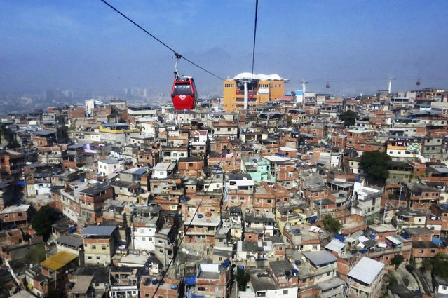 """Cable cars are seen over de Complexo de Alemao slum in Rio De Janeiro June 28, 2014. In a project called """"On The Sidelines"""" Reuters photographers share pictures showing their own quirky and creative view of the 2014 World Cup in Brazil. (Photo by Alessandro Garofalo/Reuters)"""
