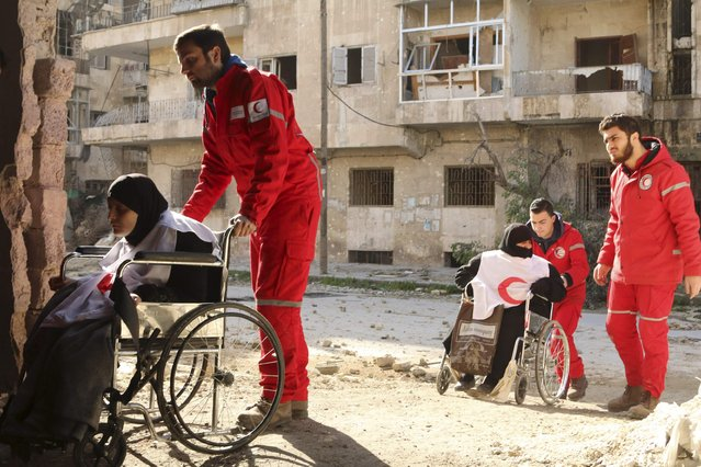 Members of the Syrian Arab Red Crescent push women on wheelchairs at the Karaj al-Hajez crossing, a passageway separating Aleppo's Bustan al-Qasr, which is under rebel control, and Al-Masharqa neighbourhood, an area controlled by forces loyal to Syria's President Bashar al-Assad February 1, 2015. (Photo by Ammar Abdullah/Reuters)