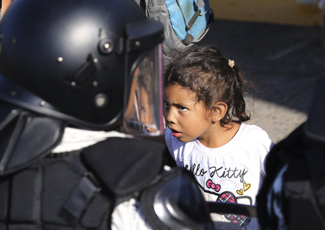 A migrant girl looks at Mexican National Guardsmen at the border crossing between Guatemala and Mexico in Tecun Uman, Guatemala, Saturday, January 18, 2020. More than a thousand Central American migrants surged onto the bridge spanning the Suchiate River, that marks the border between both countries, as Mexican security forces attempted to impede their journey north. (Photo by Marco Ugarte/AP Photo)