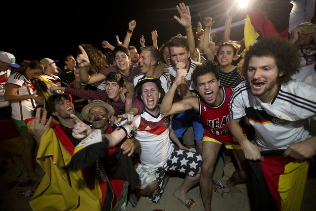 Soccer fans of the Germany national soccer team celebrate thier team's victory during a live broadcast of the final World Cup match between Germany and Argentina, inside the FIFA Fan Fest area on Copacabana beach, Rio de Janeiro, Brazil, Sunday, July 13, 2014. Mario Goetze volleyed in the winning goal in extra time to give Germany its fourth World Cup title with a 1-0 victory over Argentina. (Photo by Silvia Izquierdo/AP Photo)