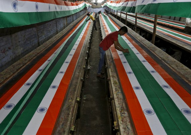 Workers make Indian national flags inside a textile printing workshop ahead of the Independence Day celebrations in Ahmedabad, India, August 10, 2015. (Photo by Amit Dave/Reuters)