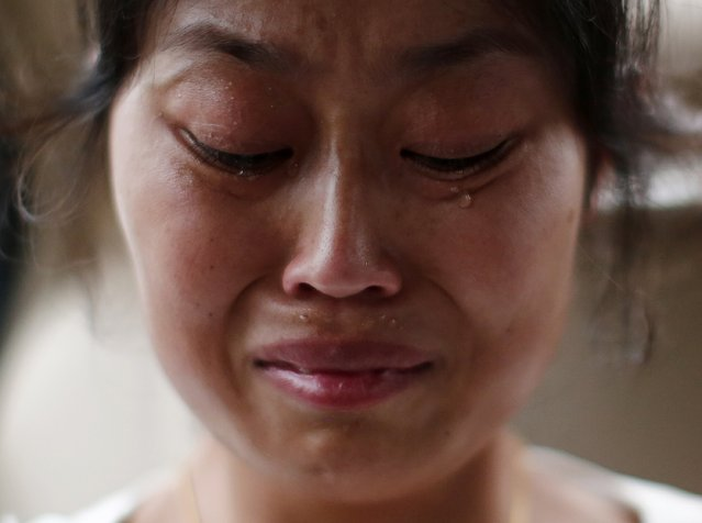 Liu Ling, whose husband was onboard Malaysia Airlines Flight MH370 which disappeared on March 8, cries during an interview with Reuters in Beijing July 18, 2014. World leaders demanded an international investigation into Thursday's shooting down of Malaysia Airlines Flight MH17 with 298 people on board over eastern Ukraine in a tragedy that could mark a pivotal moment in the worst crisis between Russia and the West since the Cold War.(Photo by Kim Kyung-Hoon/Reuters)