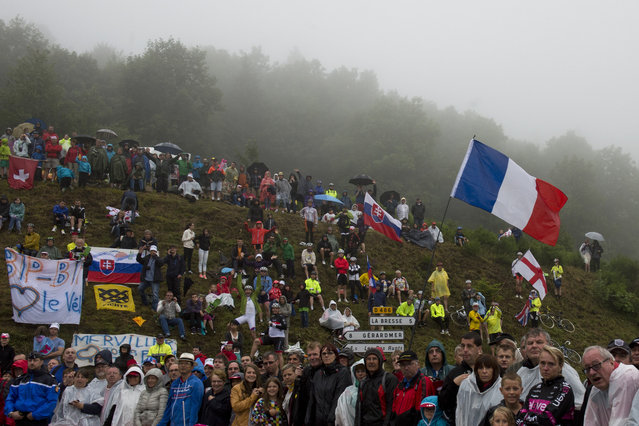 A supporter holds a French national flag along the road during the 161 km eighth stage of the 101st edition of the Tour de France cycling race on July 12, 2014 between Tomblaine and Gerardmer La Mauselaine, eastern France. (Photo by Jeff Pachoud/AFP Photo)