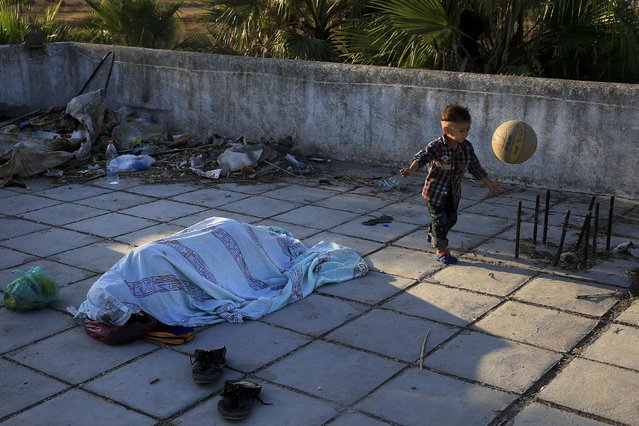 A migrant child from Pakistan plays with a ball as another migrant sleeps at the terrace of a deserted hotel on the Greek island of Kos, August 13, 2015. (Photo by Alkis Konstantinidis/Reuters)