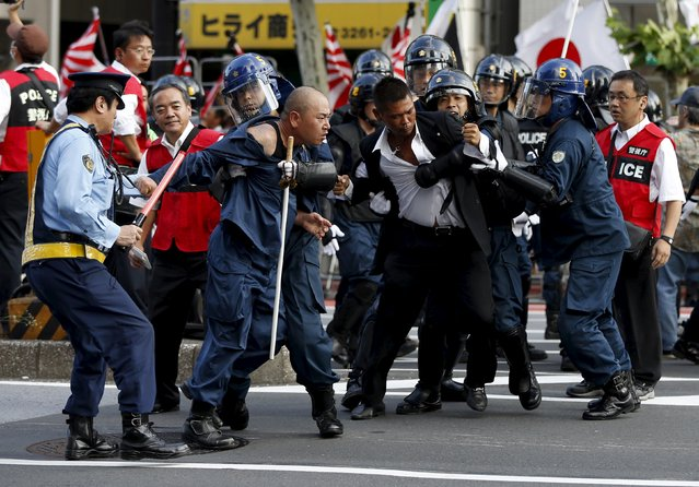 """Right-wing activists jostle with riot police officers as anti-war and anti-imperialist protesters (not pictured) march near Yasukuni Shrine in Tokyo, August 15, 2015, to mark the 70th anniversary of Japan's surrender in World War Two. Japanese Emperor Akihito marked the 70th anniversary of the end of World War Two with an expression of """"deep remorse"""" over the conflict on Saturday, a departure from his annual script which could be seen as a subtle rebuke of Prime Minister Shinzo Abe. (Photo by Issei Kato/Reuters)"""