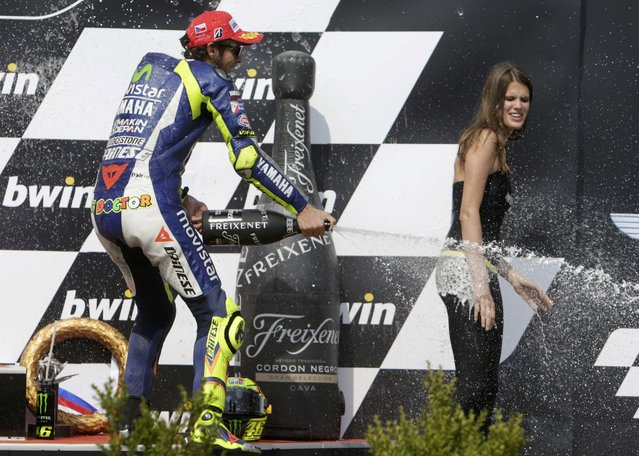 Yamaha MotoGP rider Valentino Rossi of Italy sprays champagne to a grid girl after finishing third in the Czech Grand Prix in Brno, Czech Republic, August 16, 2015. (Photo by David W. Cerny/Reuters)