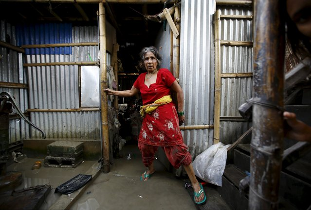 A woman walks out from her shed near floodwaters caused by heavy rainfall flowing from the swollen Bagmati River in a slum in Kathmandu, Nepal August 17, 2015. (Photo by Navesh Chitrakar/Reuters)