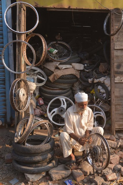 Indian mechanic, Mahinder Singh, 62, who repairs motorcycle wheels, works outside  his shop in Amritsar on June 29, 2016. Singh charges INR 100 (1.50 dollars) for each motorcycle wheel repair and earns INR 200 – 300 daily. (Photo by Narinder Nanu/AFP Photo)
