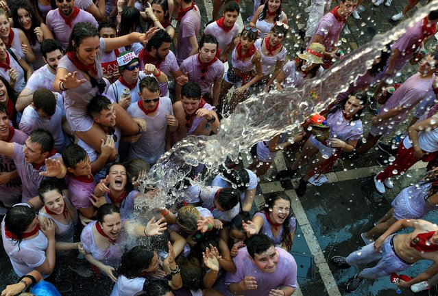 Revellers cool off with water thrown from a balcony during the start of the San Fermin festival in Pamplona, Spain July 6, 2016. (Photo by Eloy Alonso/Reuters)