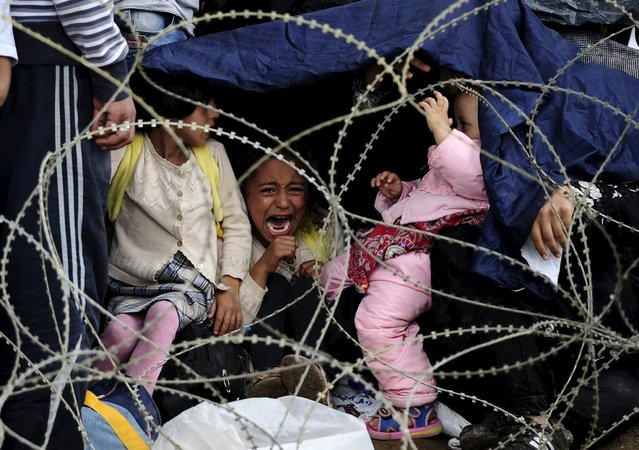 A little girl cries as she tries to take shelter from the rain on Greece's border with Macedonia, as she waits with her family to enter Gevgelija, Macedonia August 22, 2015. Police and soldiers deployed along Macedonia's southern border with Greece struggled on Saturday to control the numbers of refugees and migrants, many of them fleeing Middle East conflicts, seeking to reach western Europe. (Photo by Ognen Teofilovski/Reuters)
