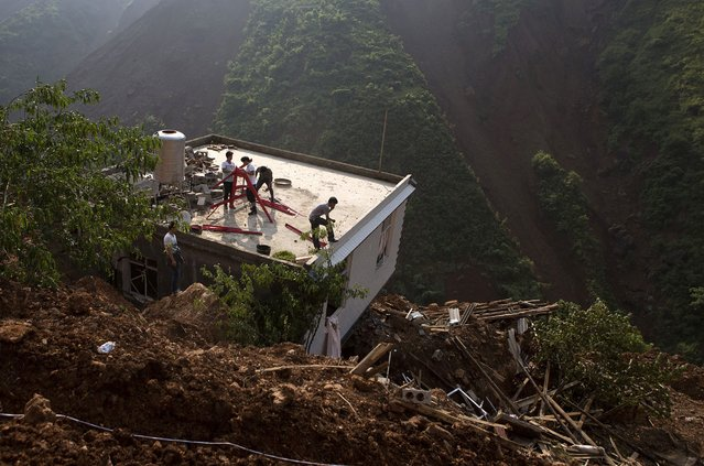 People stand atop of the roof of a damaged house seen among debris after an earthquake hit Ludian county in Yunnan province August 7, 2014. The earthquake in China on the weekend triggered landslides that have blocked rivers and created rapidly growing bodies of water that could unleash more destruction on survivors of the disaster that killed 615 people, state media reported on Thursday. (Photo by Reuters/Stringer)