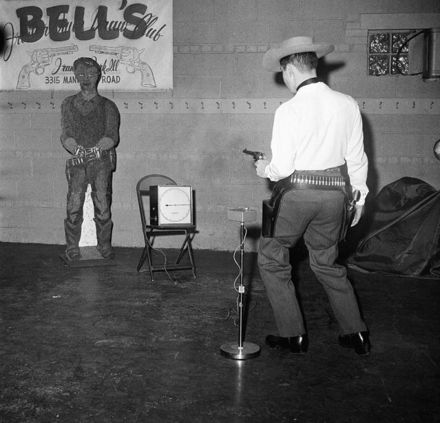 "In this January 9, 1959 file photo, Jim Bell, 17, the fastest draw in the Frontier Quick Draw Club, demonstrates his speed against a ""bad man"" target in Chicago, Ill. Jim can draw in 19/100ths of a second. The gun slingers use wax bullets which they make themselves. Live ammunition is forbidden. (Photo by Edward Kitch/AP Photo)"