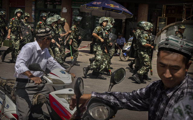 Chinese soldiers in riot gear secure the area outside the Id Kah Mosque, after Imam Jumwe Tahir was killed by assailants following early morning prayers on July 30, 2014 in old Kashgar, Xinjiang Province, China. (Photo by Kevin Frayer/Getty Images)