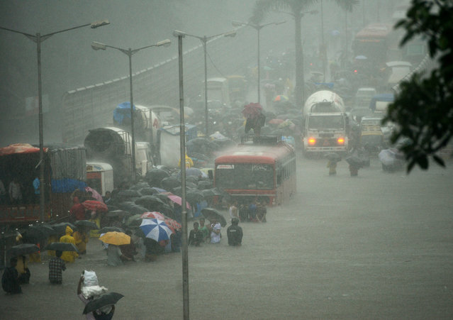 People wade along a flooded street during heavy rain showers in Mumbai on August 29, 2017. Heavy rain brought India's financial capital Mumbai to a virtual standstill on August 29, flooding streets, causing transport chaos and prompting warnings to stay indoors. Dozens of flights and local train services were cancelled as rains lashed the coastal city of nearly 20 million people. (Photo by Punit Paranjpe/AFP Photo)